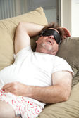Lazy Man Asleep on Couch — Stockfoto