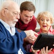 Stock Photo: Seniors and Adult Son with Tablet PC