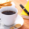Hot coffee cup with bread on the work space — Stock Photo