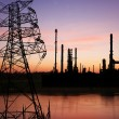 High voltage pose with petrochemical oil refinery plant - Stock Photo