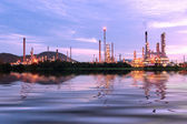 Green grass field with scenic of petrochemical oil refinery plan — Stock Photo