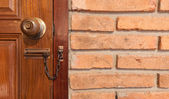 Wooden door with locker and red brick — Stock Photo