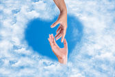 Hand reaching to someone to love on heart in the blue sky cloud — Stock Photo
