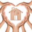 Hands make heart shape with wood house — Stock Photo