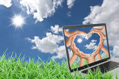 Notebook computer on grass with blue sky — Stock Photo