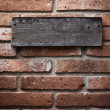 Wooden sign on vintage brick wall — Stock Photo