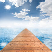 Wooden bridge with cloudy blue sky and the blue sea — Stock Photo