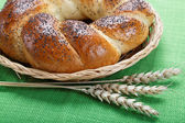 Fresh bread with ears of wheat on a green canvas. — Stock Photo