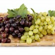 Fresh grape fruits with green leaves isolated on white backgroun — Stock Photo