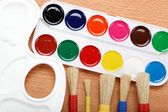 Paint, palette and brushes on a wooden table. — ストック写真