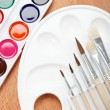 Paint, palette and brushes on a wooden table. — Foto Stock