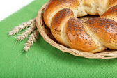 A fresh loaf of bread sprinkle with poppy seeds on a green canva — Stock Photo