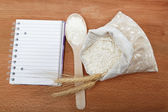 Recipe Book and flour in a sack with a spoon on a wooden table. — Stok fotoğraf