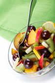 Fresh fruits salad on a green canvas. — Stock fotografie
