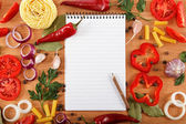Notebook for recipes, vegetables and spices on wooden table. — Stock Photo