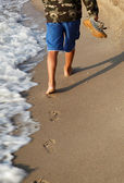 Boy walk on the sandy beach near the sea and leaves traces. — Foto de Stock