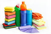 Detergent bottles, rubber gloves and cleaning sponge on a white — Stock Photo