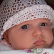 Close-up portrait of a beautiful baby girl in a white knitted ca — Stock Photo #13940035