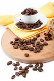 Cup with coffee beans and a bunch of cinnamon on a wooden board. — Stock Photo