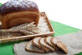 Fresh bread with ears of wheat on the canvas. — Stock Photo