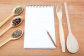 Notebook for recipes and spices on wooden table — Stockfoto