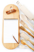 Notebook for recipes, cooking utensils and cinnamon on wooden bo — Stock Photo