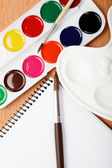 Paint, palette, notebook and brushe on a wooden table. — Stock Photo