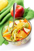Fresh fruits salad on a green canvas. — Stock Photo