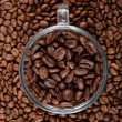 Stock Photo: Glass coffee cup on background of coffee beans.