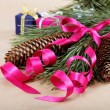 Photo: Christmas decorations. Spruce branch with cones, pink ribbon and