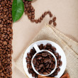 Cup with coffee beans and cinnamon sticks on sackcloth. — Stock Photo #17413693