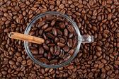 Copo de vidro com grãos de café e paus de canela. — Fotografia Stock