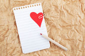 Sheet of notebook with a heart and pencil on crumpled paper. Val — Stock Photo