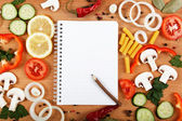 Notebook for recipes, vegetables and spices on wooden table. — Foto Stock