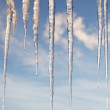 Icicles in the sunny day against a blue sky with white clouds. — Stock Photo #19384939