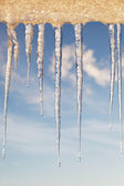 Icicles in the sunny day against a blue sky with white clouds. — Foto de Stock