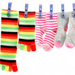 Colorful socks attached clothespin hanging from a rope. - Stock Photo