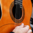 Guitarist hand playing acoustic guitar. - Stock Photo
