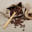 Coffee beans in a spoons on sacking. — Stock Photo