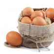 Brown eggs in canvas sack isolated on a white background - Stock Photo