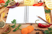 Notebook for recipes, vegetables and spices on wooden table. — Photo