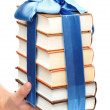 Stock Photo: Book as gift. stack of books in female hand on white backg