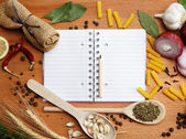 Notebook for recipes and spices on wooden table — Photo