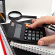 Hands holding the handle and pressing calculator buttons over do — Stock Photo