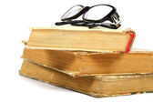 Stack of old books and glasses on a white background. — Stock Photo