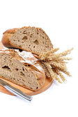 Two halves a loaf of rye bread with a knife and wheat ears. — Stock Photo