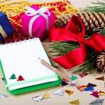 Weihnachts-Dekorationen, Geschenke und ein Notebook für Glückwünsche — Stockfoto