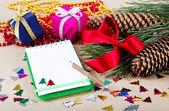 Adornos de navidad, regalos y un cuaderno para felicitaciones. — Foto de Stock