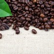 Roasted coffee beans on sackcloth. — Stock Photo #37426501