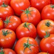 Stock Photo: Fresh red tomato in drops of water as backdrop.